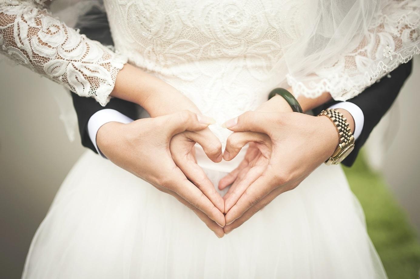 Brautpaar formt mit Händen ein Herz