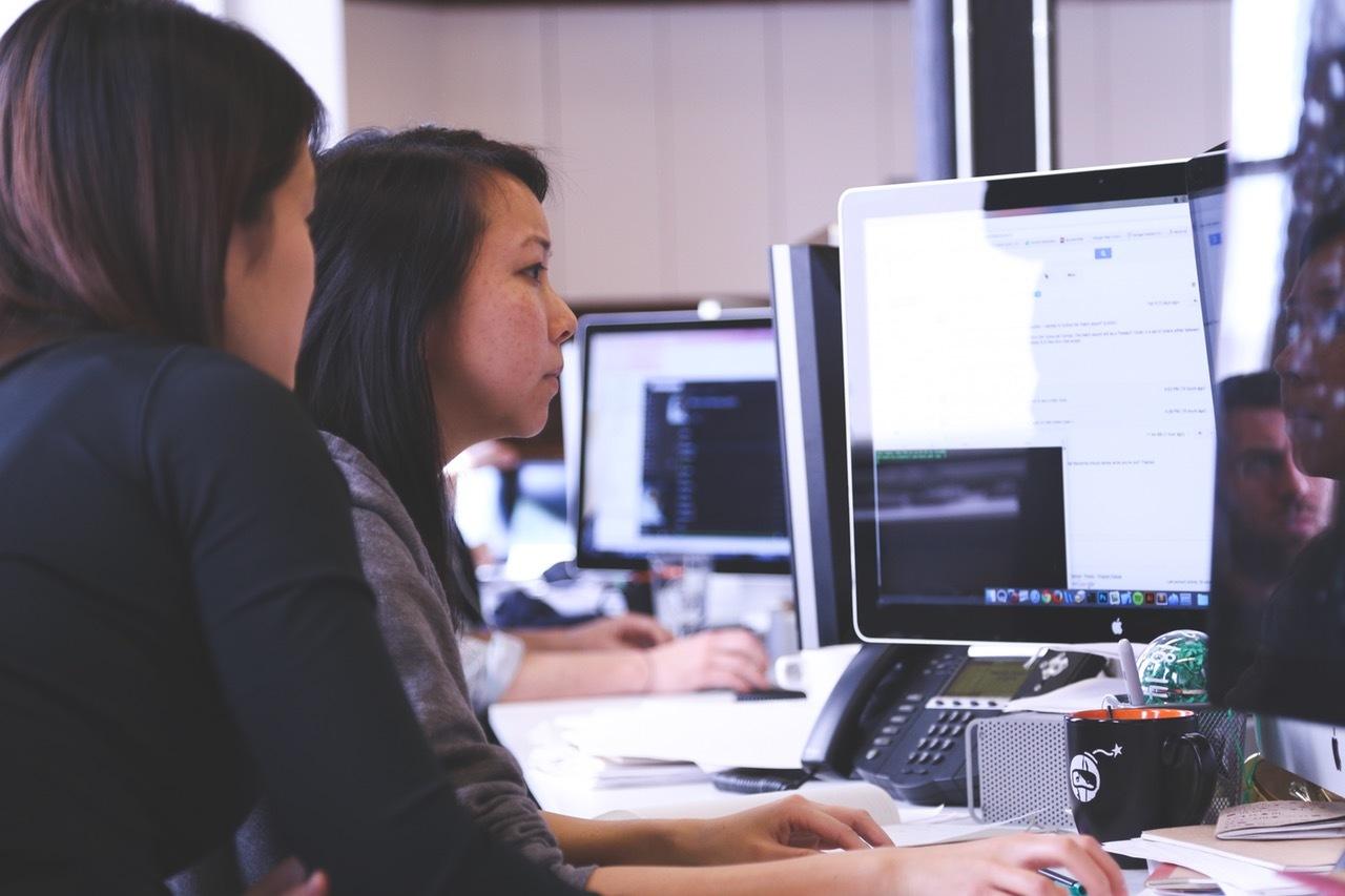 Zwei junge Frauen schauen auf den Computerbildschirm.