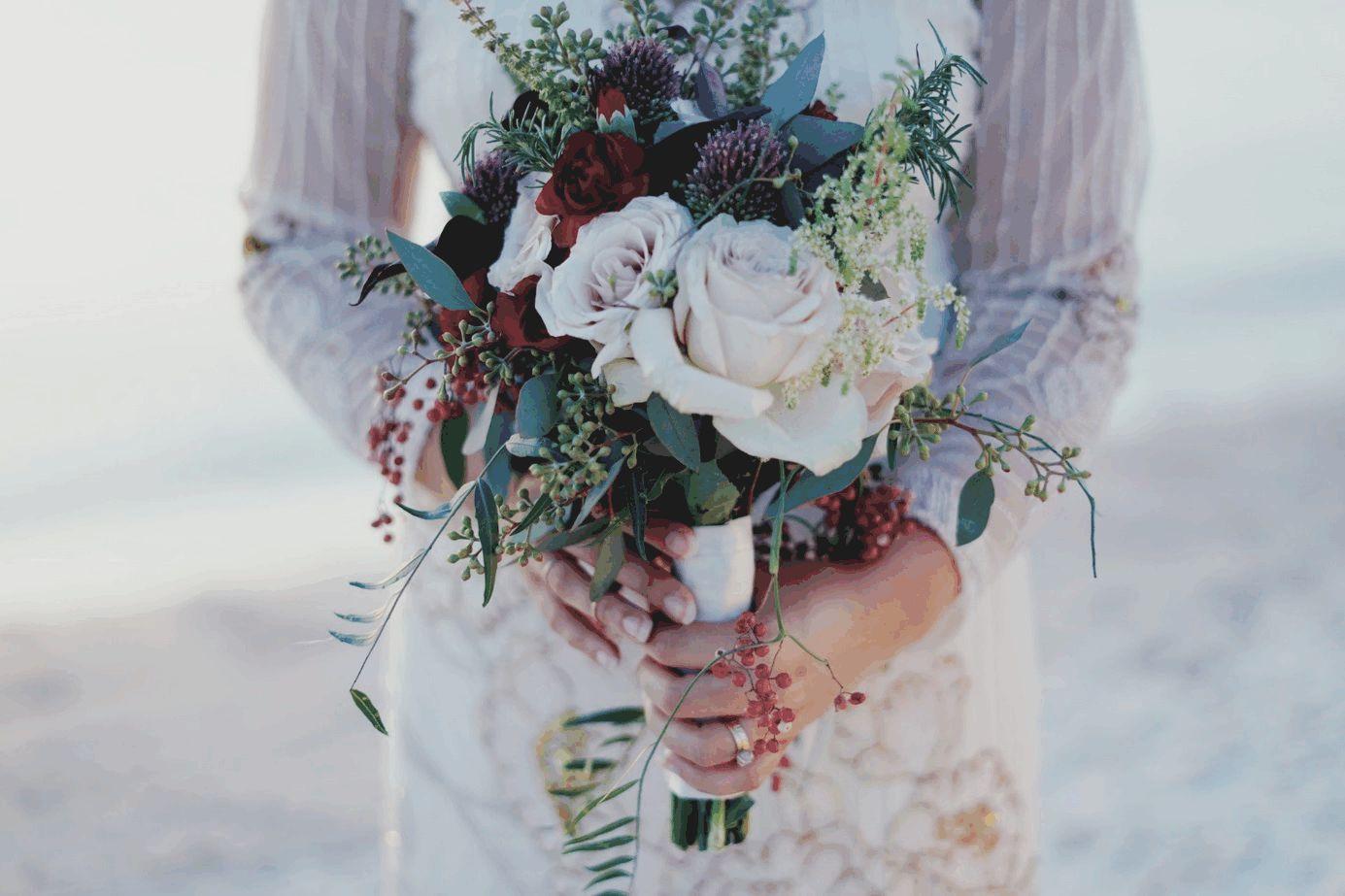 Braut am Strand mit buntem Blumenstrauß
