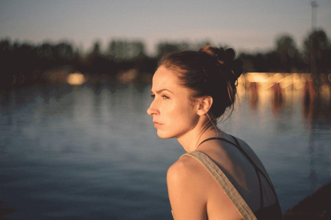 Frau steht an See und schaut in die Ferne.