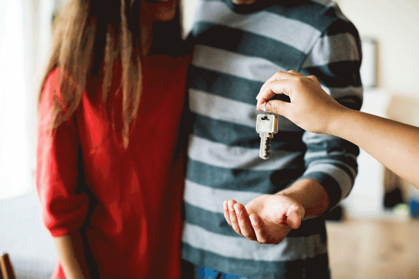 Paar erhält Schlüssel von nicht sichtbarer Person