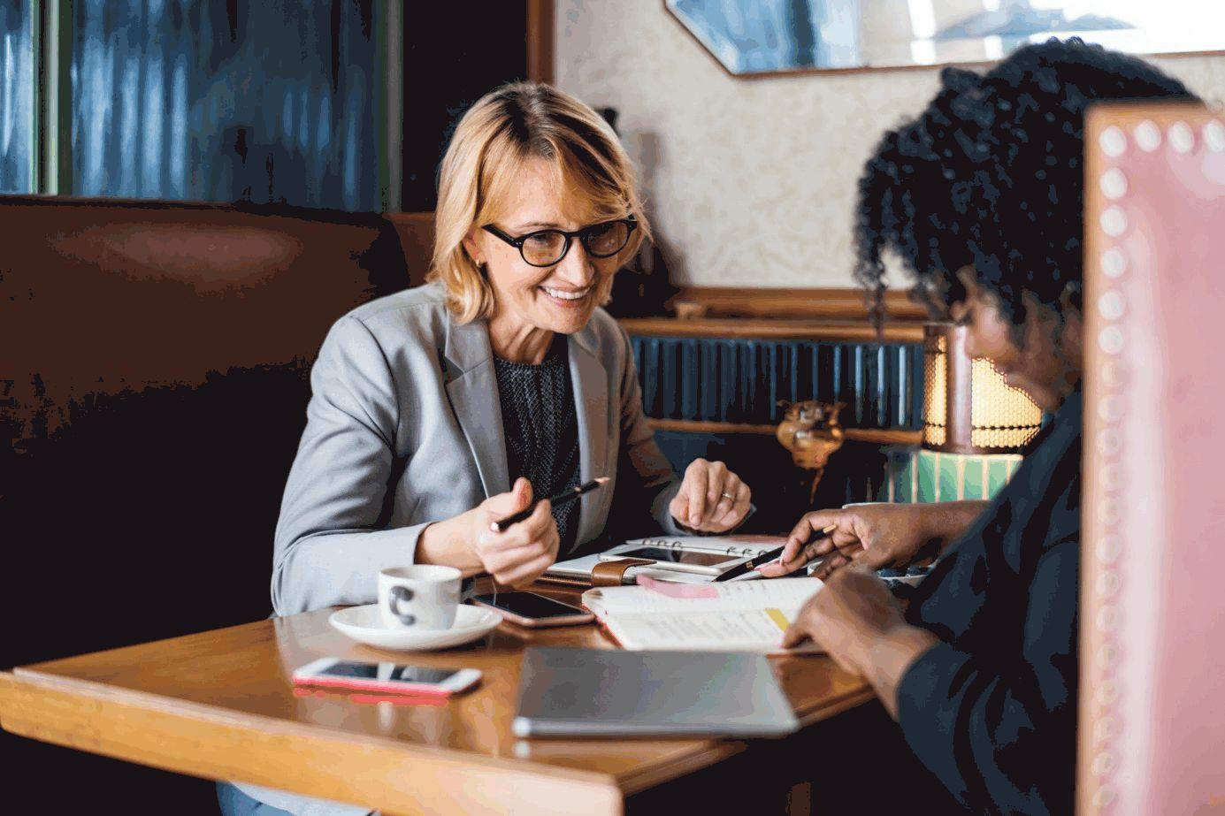Zwei Frauen an einem Tisch mit Dokumenten