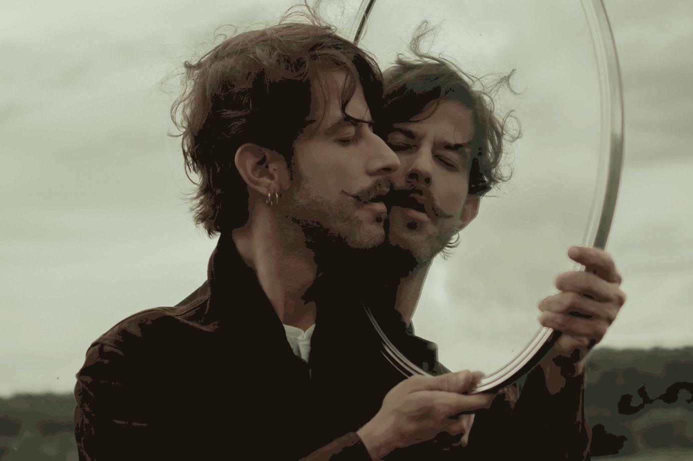Schöner Mann hält einen Spiegel vor sein Gesicht