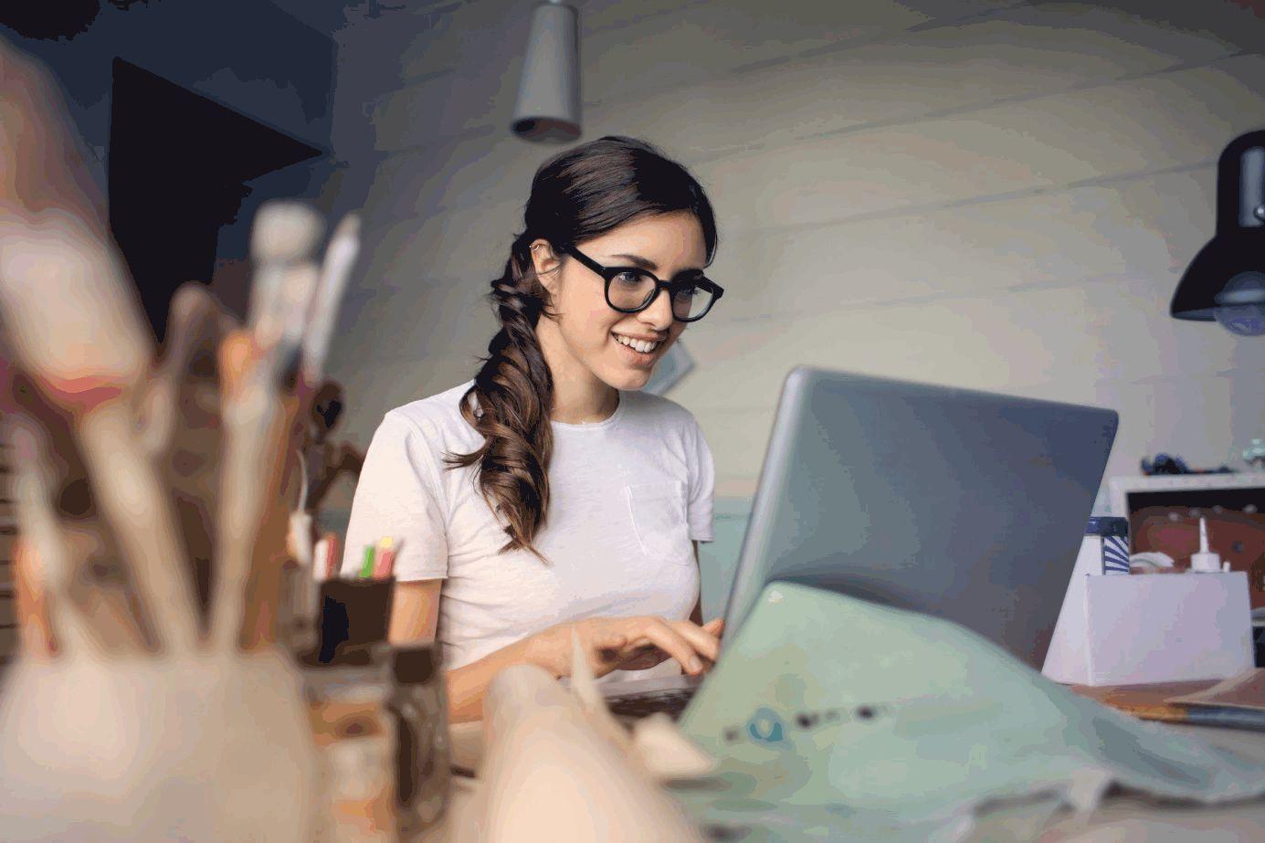 Junge Frau mit markanter Brille arbeitet an Laptop