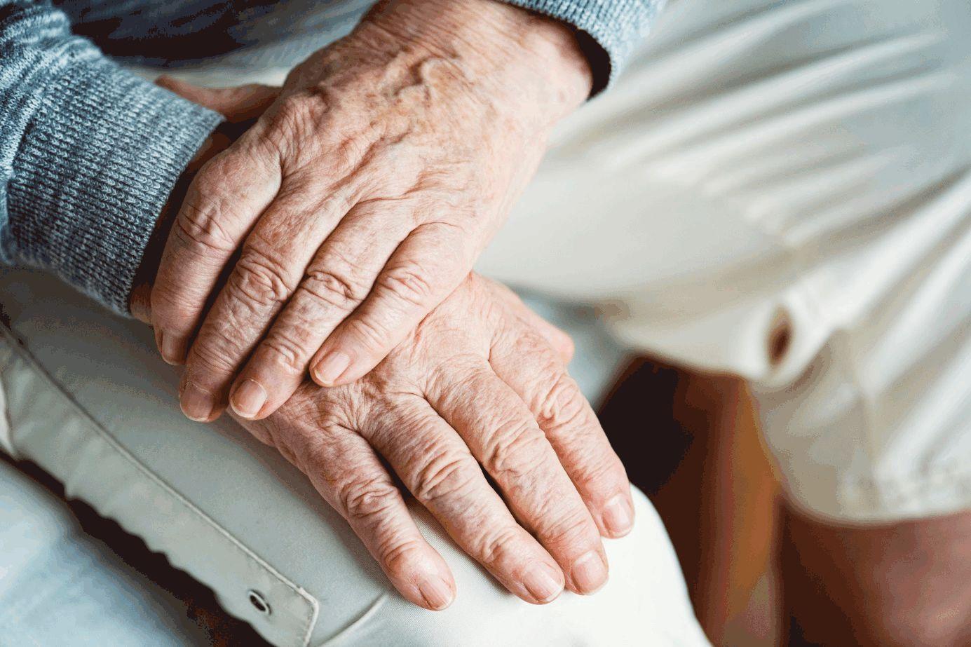 Bildauschnitt mit linker über rechter Hand eines älteren Menschen