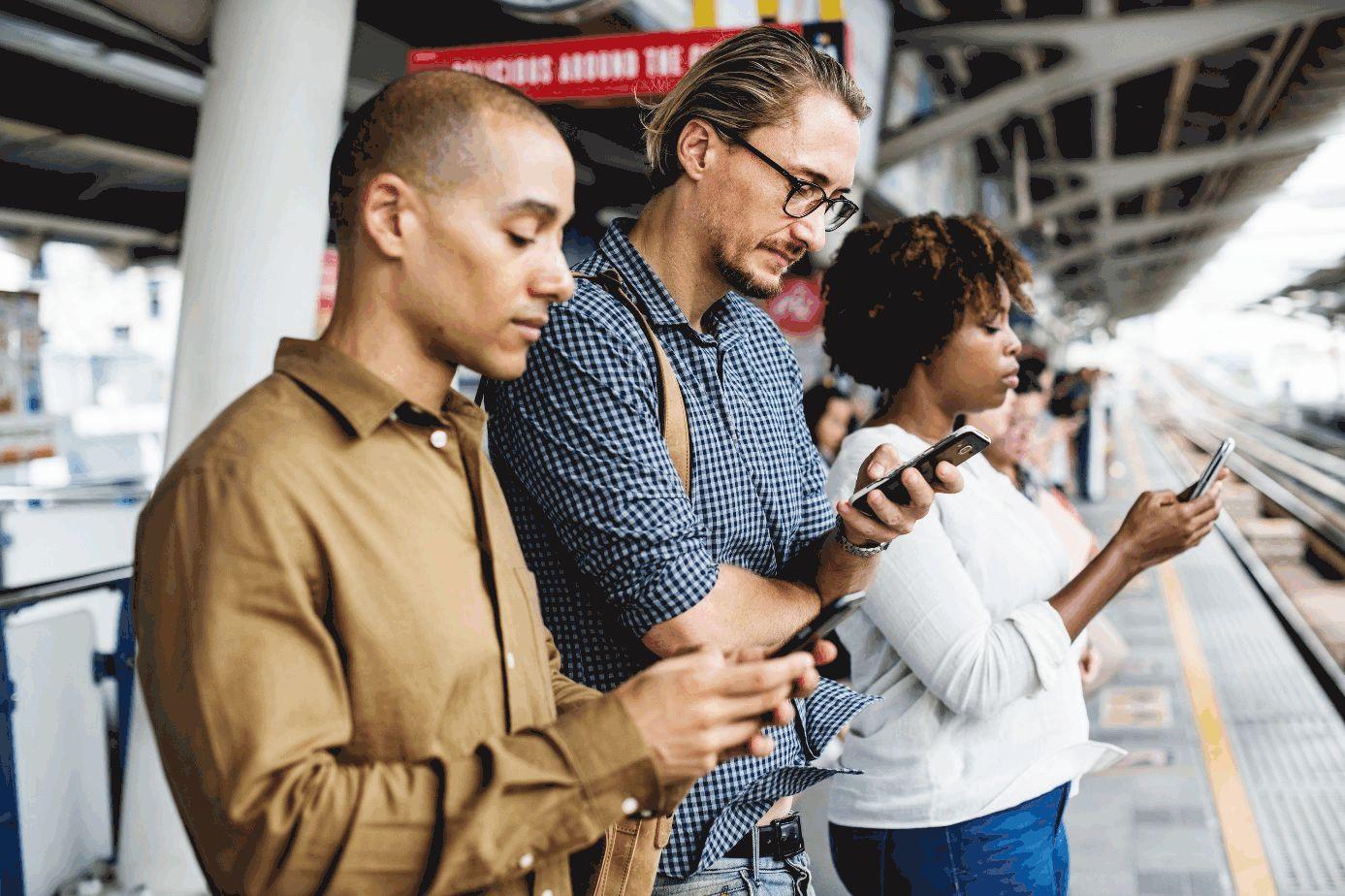 Menschen auf Bahnsteig starren auf ihr Smartphone