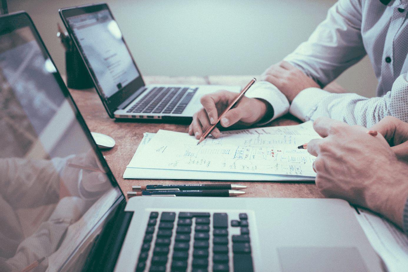 Zwei Menschen sitzen an einem Tisch vor Computern und planen auf Papier
