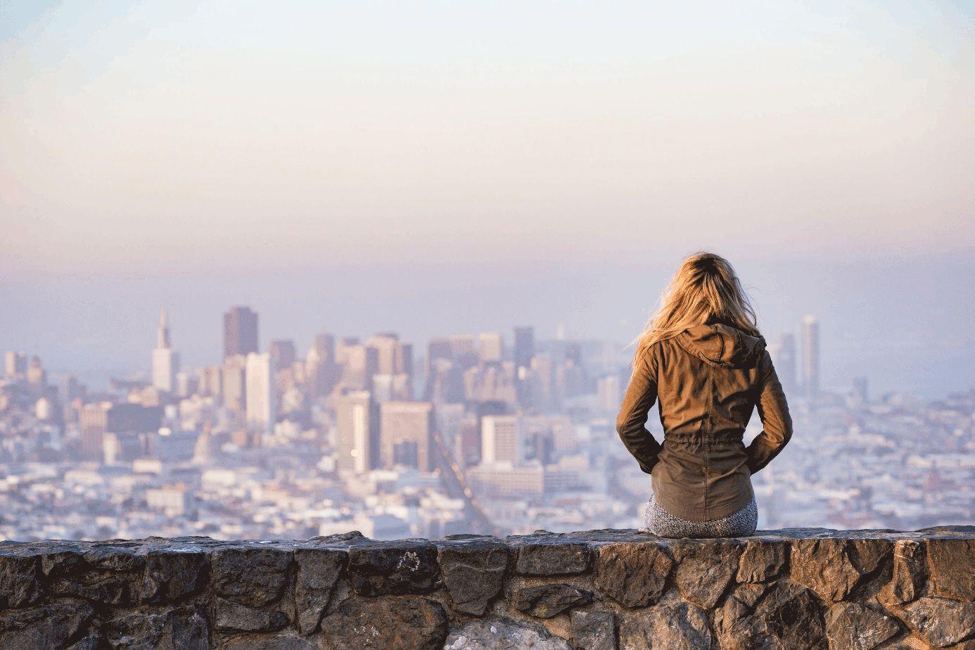 Junge Frau steht auf einer Erhöhung und blickt auf die Skyline einer Großstadt.