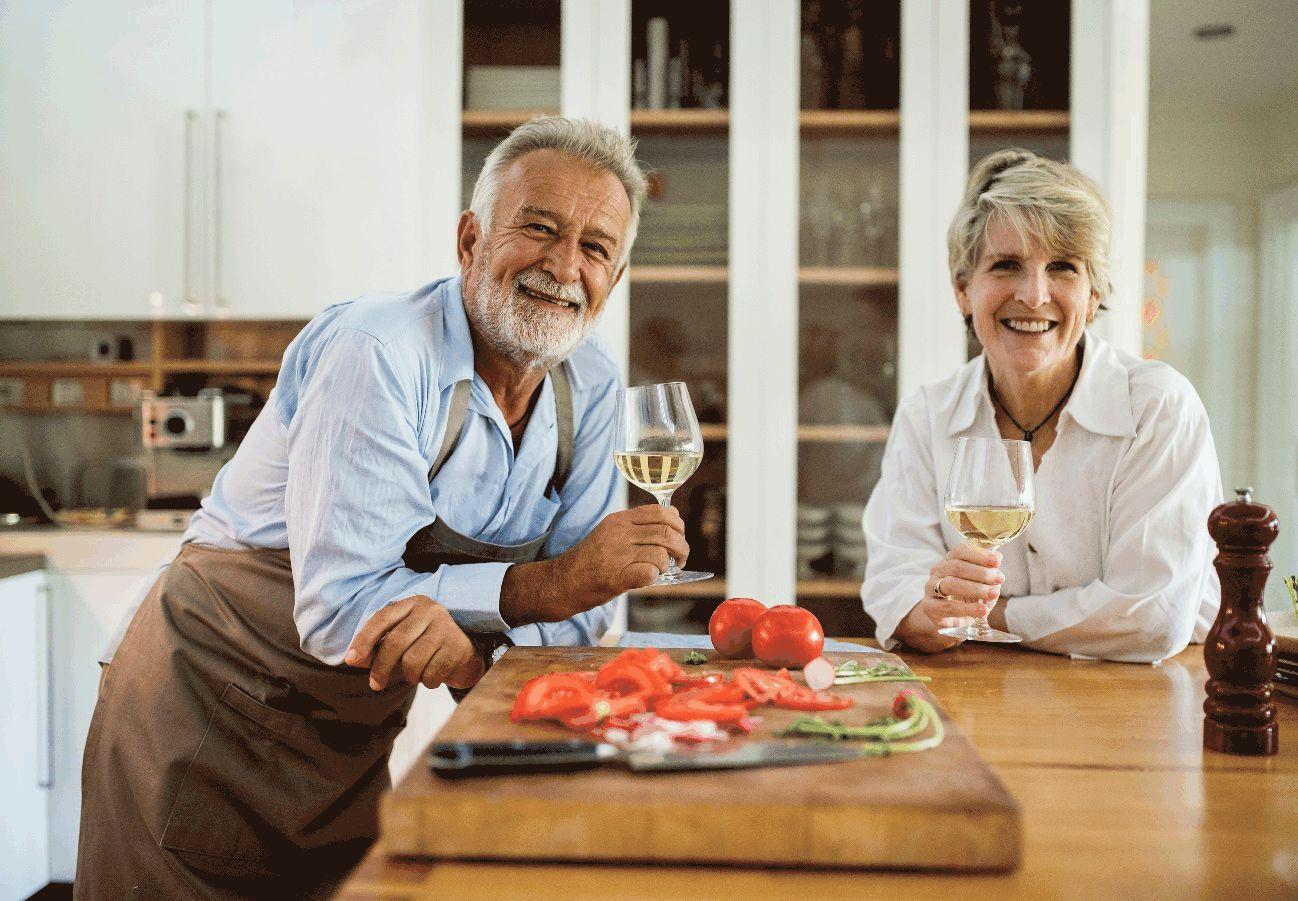 Älteres Ehepaar trinkt in einer Küche Wein.