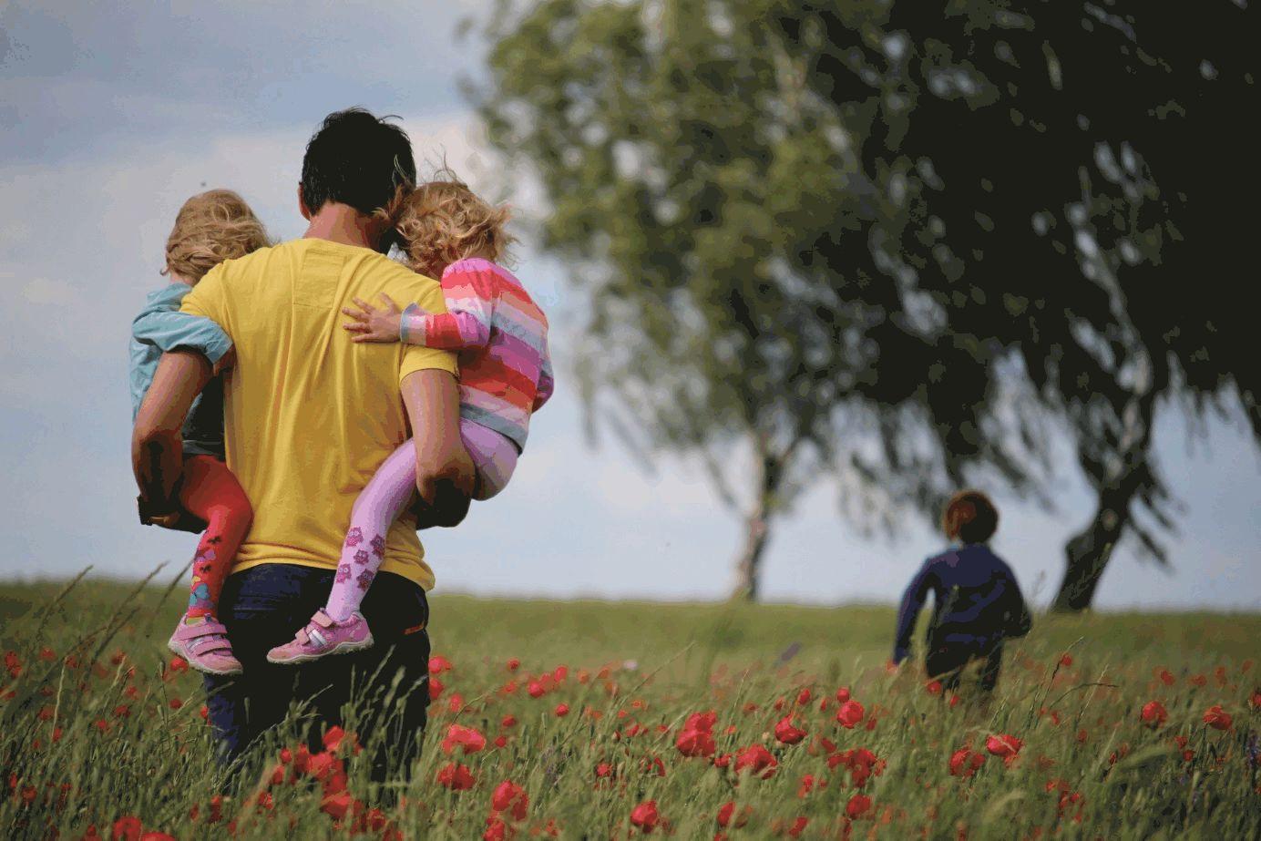 Vater mit drei Kindern auf Mohnblumenwiese