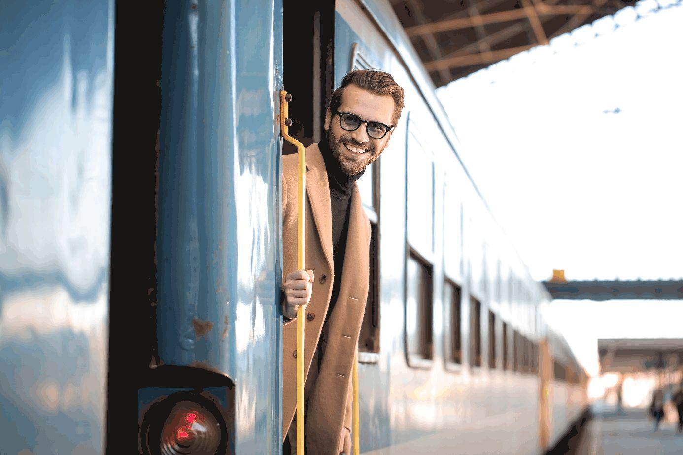 Mann schaut lächelnd aus stehendem Zug