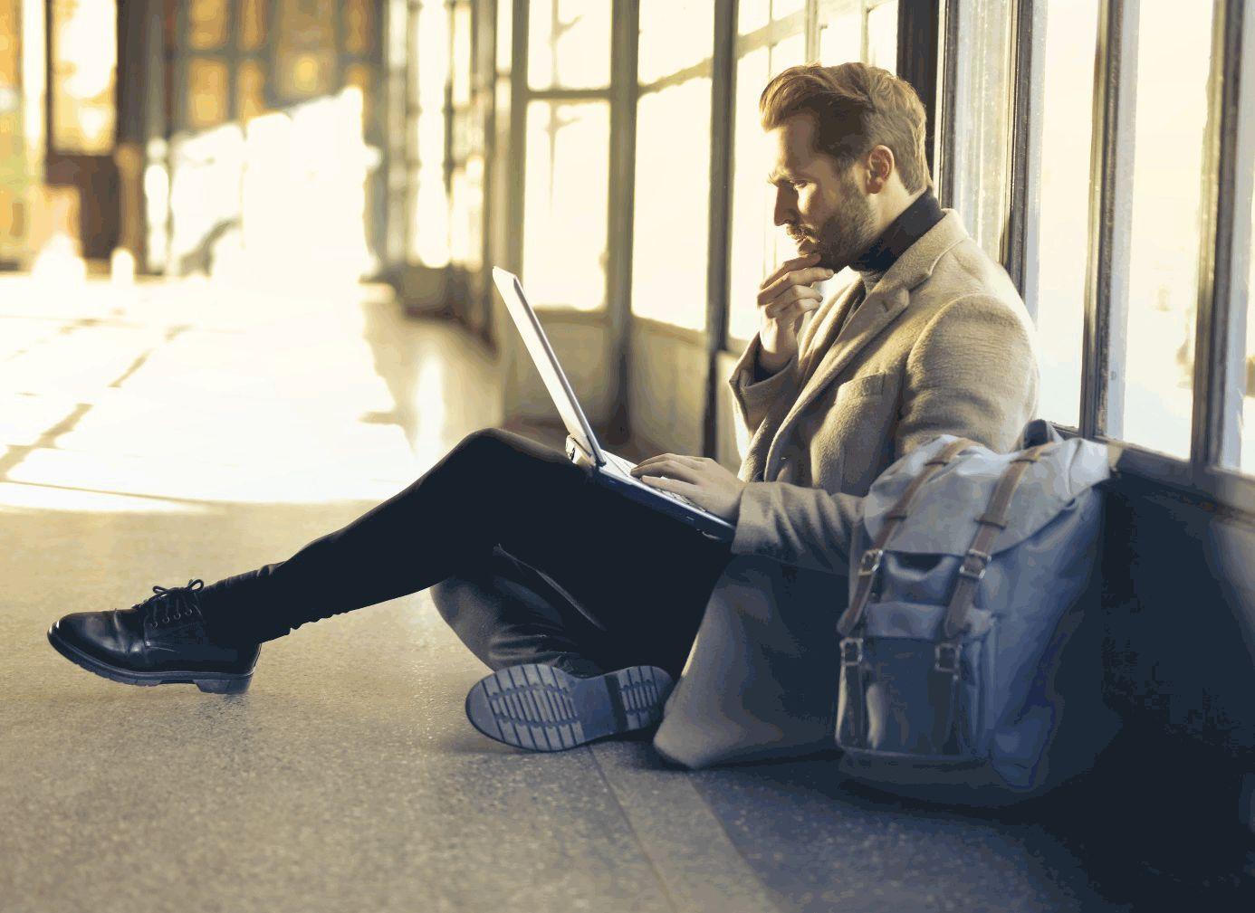 Mann sitzt mit Laptop auf dem Boden in einem leeren Raum.