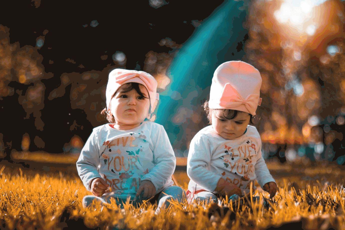 Zwillinge mit rosa Mützen sitzen im Gras