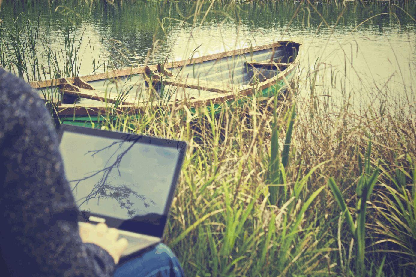Mann mit Laptop sitzt am Flussufer mit Ruderboot.