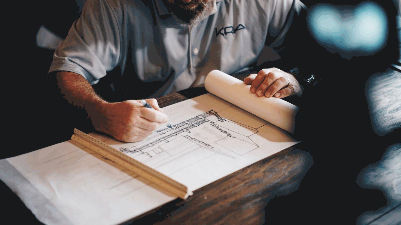 Architekt bei der Arbeit mit Zeichnung und Maßstab.