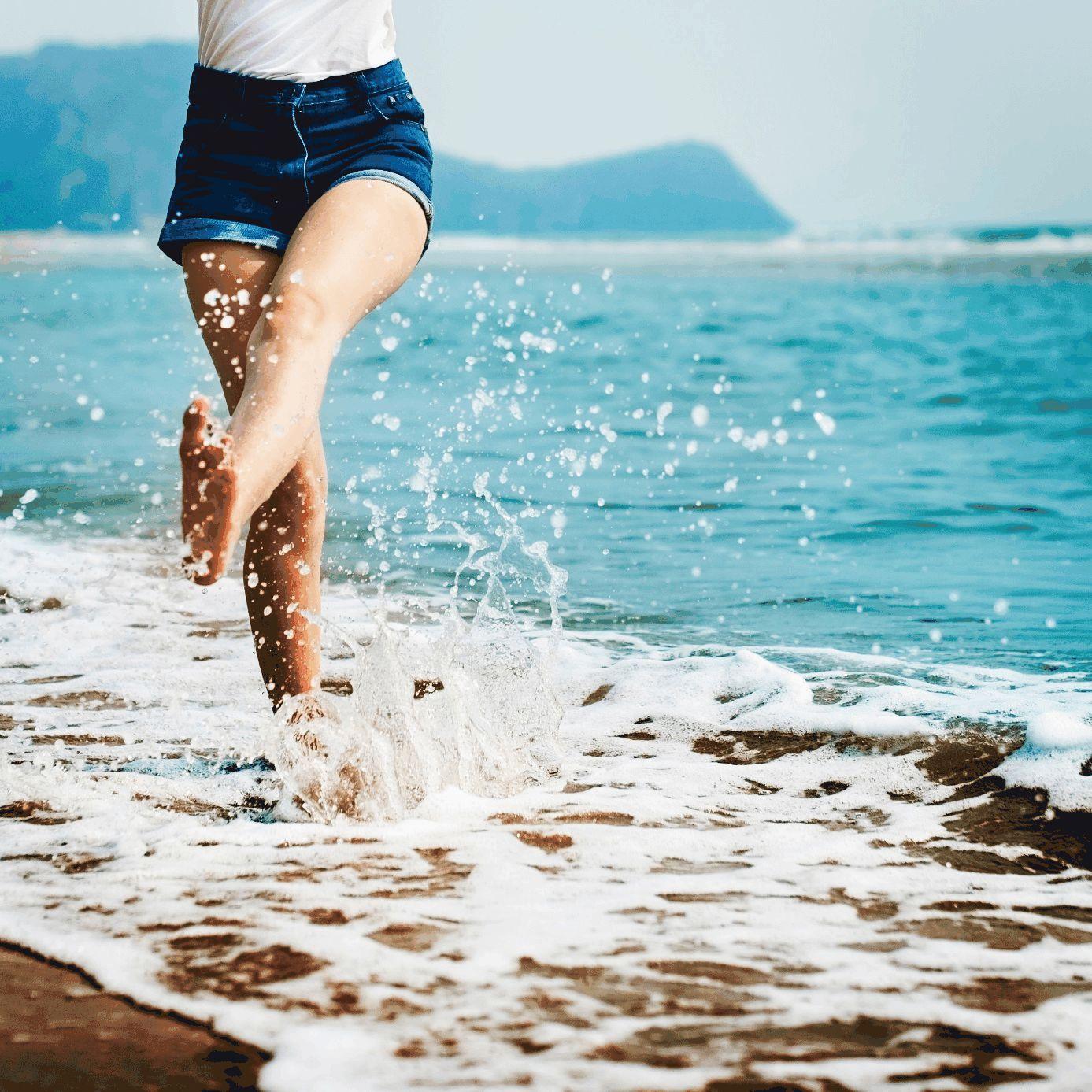 Frau am Meeresstrand spritzt mit Bein Wasser weg.
