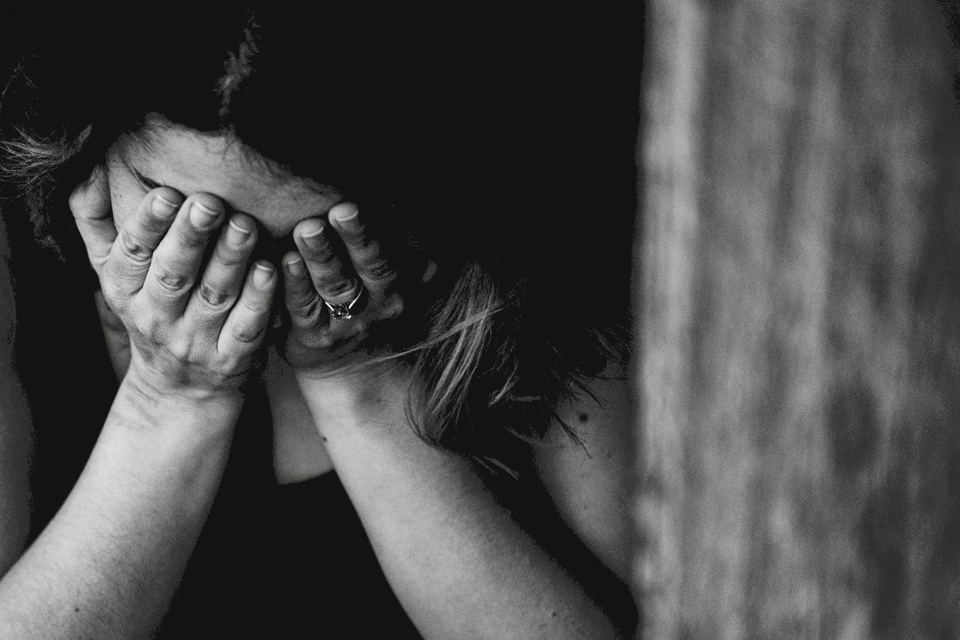 Frau legt verzweifelt ihren Kopf in die offenen Hände